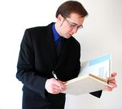 Checking finances. One businessman standing checking business papers Royalty Free Stock Image