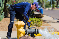 Checking The Fire Hydrant. A member of the fire department tests the flow of a fire hydrant. Can be a routine check or part of training Stock Photography