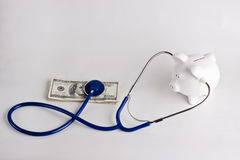Checking the health of your savings. Piggy bank with stethoscope checking on money Royalty Free Stock Image