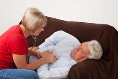 Checking heart. Home nurse checking heart of elderly man Royalty Free Stock Photo