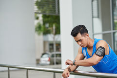 Checking Heart Rate after Training. Waist-up portrait of pensive Vietnamese man checking his heart rate on fitness tracker after intensive outdoor training Stock Image