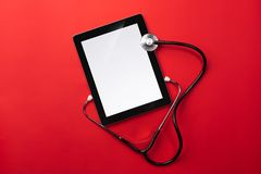Checking heartbeat on a digital tablet using a stethoscope stock image