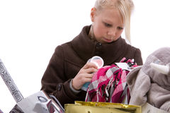 Checking her purchases. Pretty blond girl checking the contents of her shopping bags Royalty Free Stock Photos