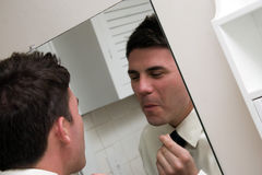 Checking Himself in the Mirror Royalty Free Stock Photos