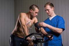 Checking his blood pressure. Shot of a men sitting on a stationary bike and looking at his arm while medic is checking his blood pressure stock images
