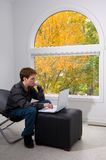 Checking his email. Teen male working with a notebook computer with fall foliage visible through a large window Royalty Free Stock Image