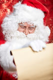 Checking his special list. Traditional Santa Claus sitting Stock Photo