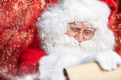 Checking his special list. Traditional Santa Claus sitting Royalty Free Stock Photography