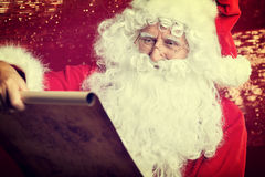 Checking his special list. Traditional Santa Claus sitting Royalty Free Stock Photos
