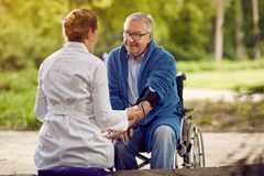 Checking the hypertension assessment of blood pressure elderly m. Nurse checking the hypertension assessment of blood pressure elderly men in wheelchair Royalty Free Stock Photos