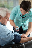 Checking the hypertension. Young attractive nurse checking the elderly man's hypertension Stock Image