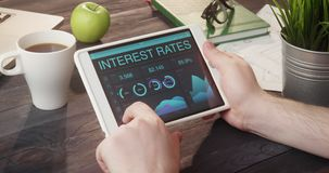 Checking interest rates data using tablet computer at desk
