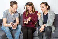 Checking internet gossip on phone Royalty Free Stock Photos