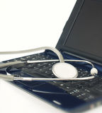 Checking laptop problems. With stethoscope on white background Royalty Free Stock Photos