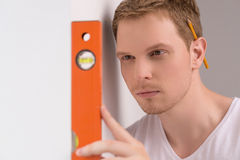 Checking the level. Confident craftsperson checking the spirit level of wall royalty free stock photography