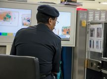Checking luggage at the airport. MALAYSIA, PENANG, NOV 14 2017, Checking luggage at the airport. A policeman watches a monitor baggage scanner stock photos