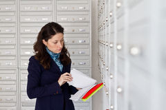 Checking the mail. Woman checking her mail next to mailboxes Stock Image