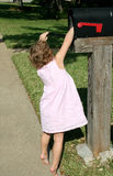 Checking the Mail. A little girl reaches into the mailbox to check if the mail has arrived Stock Photo