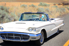Checking Makeup in Thunderbird Convertible. A pretty lady in a  Classic 1960 shiny white Ford Thunderbird Convertible on a country road out in the middle of no Stock Photography