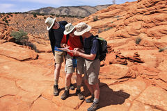 Checking the Map. Three hikers check their location en route to The Wave in the Coyote Buttes section of the Paria Canyon-Vermilion Cliffs Wilderness in northern Royalty Free Stock Image