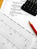 Checking medical bills. A concept photograph of going through items on a medical hospital bill.  taken with ECG graph, calculator and pencil.  Vertical format Royalty Free Stock Photo