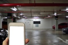 Checking a mobile phone underground in a parking lot. Checking a mobile phone underground is a common habit in a modern life. White area on the phone can be royalty free stock photo