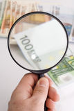Checking money. With magnifying glass Stock Photography