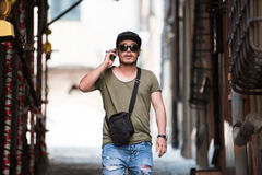 Checking my cellphone. A young Italian guy walking on the streets of Italy and checking his cellphone for new messages Royalty Free Stock Images