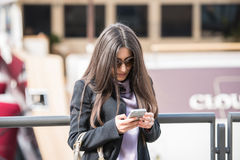 Checking my messages. Beautiful young brunette woman with fashionable sunglasses and dressed in a business casual work suit checking her messages on her royalty free stock photography
