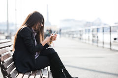 Checking my messages. A young brunet woman checking her smartphone for messages and browsing the internet royalty free stock photos