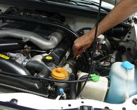 Checking Oil Dipstick. A male's hand is reaching for the dipstick to check the quality and quantity of oil in an automotive engine, under the hood of a white Stock Images