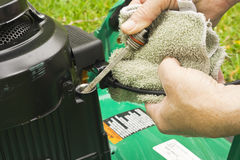 Checking oil on a lawn mower Royalty Free Stock Image