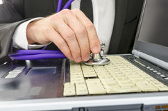 Checking old laptop with stethoscope Royalty Free Stock Images