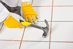 Checking old tiles base with hammer Royalty Free Stock Photos