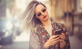 Checking out the latest buzz on social media. Woman in city using phone stock photo