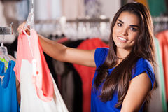 Checking out some clothes. Beautiful young woman checking out some clothes at the mall and smiling royalty free stock images