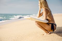 Checking out the waves. Beautiful and sexy surfer girl holding a surfboard and checking the waves Stock Photos
