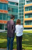Checking papers. Young boy and girl checking some papers in front of an office building; business couple analising some documents Stock Photo