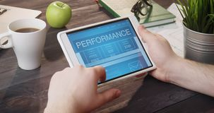 Checking performance info using digital tablet at desk stock footage