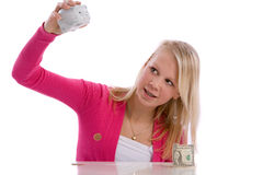 Checking the piggybank contents. Young cute teenage girl checking the contents of her piggybank Stock Image