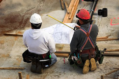 Checking the Plan. Two men reviewing the blueprint during construction royalty free stock photography