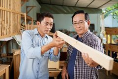 Checking plank evenness. Carpenters checking evenness of wooden plank when working in studio royalty free stock photos