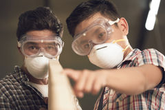 Checking plank. Teenage boy and his father in masks and goggles checking in the wooden plank is even Royalty Free Stock Photos