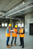 Checking Points with Construction Inspector. Group of three workmen discussing development progress with foreman inspector on construction site stock image