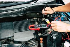 Checking power of battery by clamp meter,. Maintenance car by yoursalf, Monthly check Stock Photos