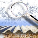 Checking for the presence of asbestos, one of the most dangerous construction materials, in our buildings - concept image with a. Magnifying glass agaisnt an royalty free stock photography