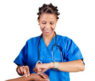 Checking pulse. African doctor or nurse checking patient's pulse Stock Photo