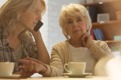 Checking the pulse. Adult women checking her older mother`s pulse and calling the doctor Royalty Free Stock Photography