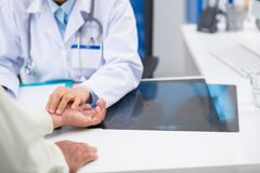 Checking pulse. Doctor touching hand of her patient to check his pulse stock photo