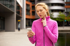 Checking pulse. Exercise woman timing her pulse on her phone stock photography